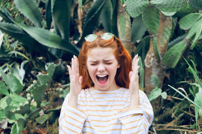 Woman gesturing while shouting against plants