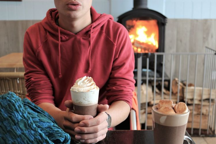 Midsection of teenage boy holding drink