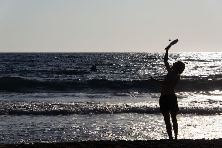 People playing, swimming in the waves in the island of Patmos, Greece in summer time Arms Raised Beach Beauty In Nature Full Length Horizon Horizon Over Water Human Arm Land Leisure Activity Lifestyles One Person Outdoors Real People Scenics - Nature Sea Silhouette Sky Standing Water