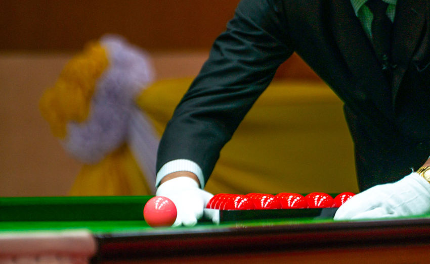 Midsection of man arranging balls on pool table