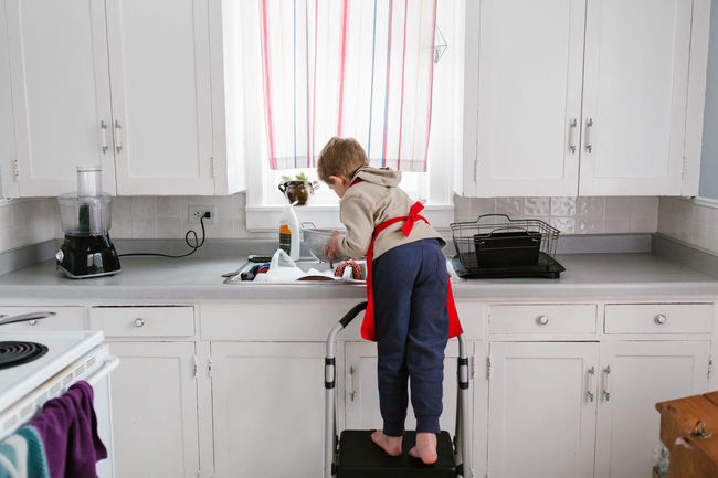 Dishes Sink Washing Boy In Kitchen Casual Clothing Child Cooking Child In Kitchen Childhood Colander Day Domestic Kitchen Domestic Life Domestic Room Holding Home Interior Indoors  Kitchen One Person People Real People Red Apron Standing