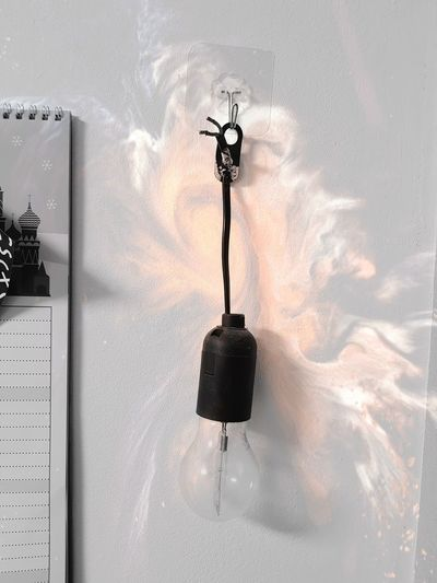 Electric lamp hanging on wall