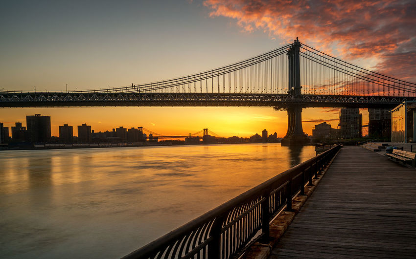 Manhattan bridge over east river against sky during sunrise seen from brooklyn park