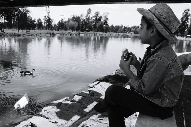 Boy having snack while looking at ducks in swimming lake