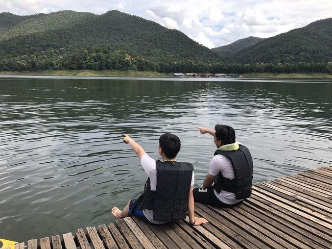 เพื่อนคุยกัน Two People Lake Rear View Sitting Relaxation Day Water Mountain Togetherness Casual Clothing Full Length Outdoors Boys People Child Adult Real People Women Nature Men Vacations MaeTang