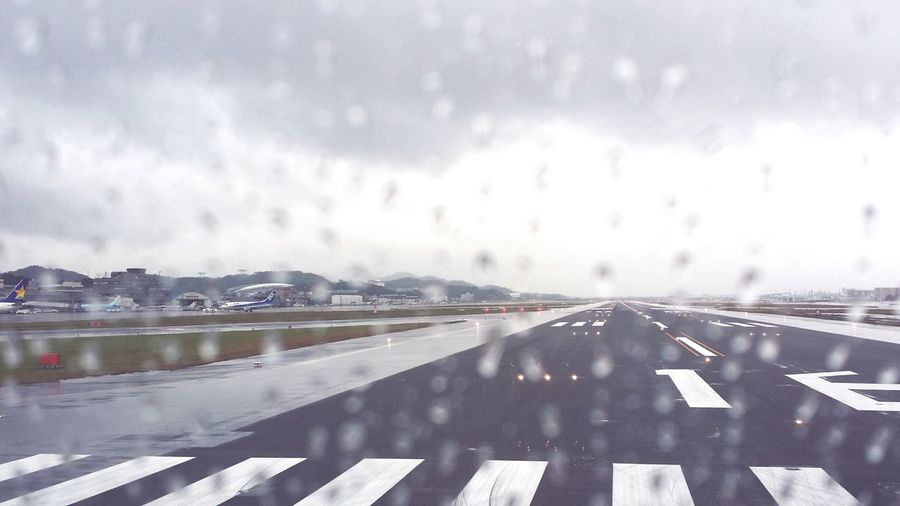 It's raining on the runway. Overcast Rain Bridge - Man Made Structure Storm Cloud No People Connection Architecture Water Urban Skyline Outdoors Nature Day Rain Rainy Days Window Plane The Way Forward People Sky Shelf Retail  Fly Cloud Airplane Cloud - Sky