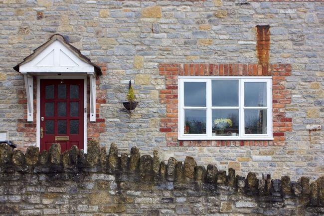 springtime daffodils in house's window Bright Door Home House Quaint  Springtime Stone Window