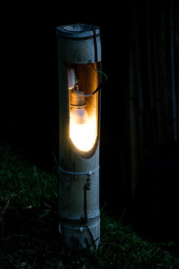 Close-up of illuminated electric lamp on field