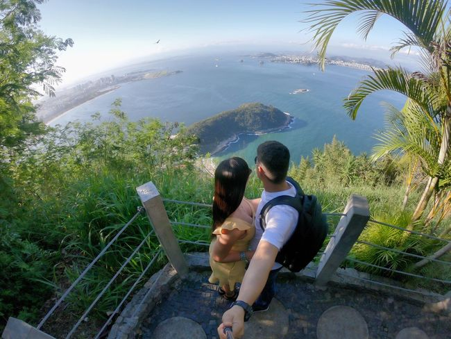 On top of Pão de Açúcar Gopro Vacation Travel Rio De Janeiro Brazil Real People Leisure Activity Two People Casual Clothing Lifestyles Plant Women Men Nature Togetherness Day High Angle View People Rear View Adult Tree Bonding Young Women Water Sitting