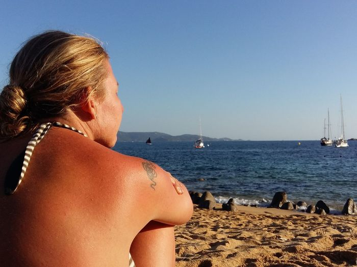 Rear view of woman sitting at beach against clear sky on sunny day