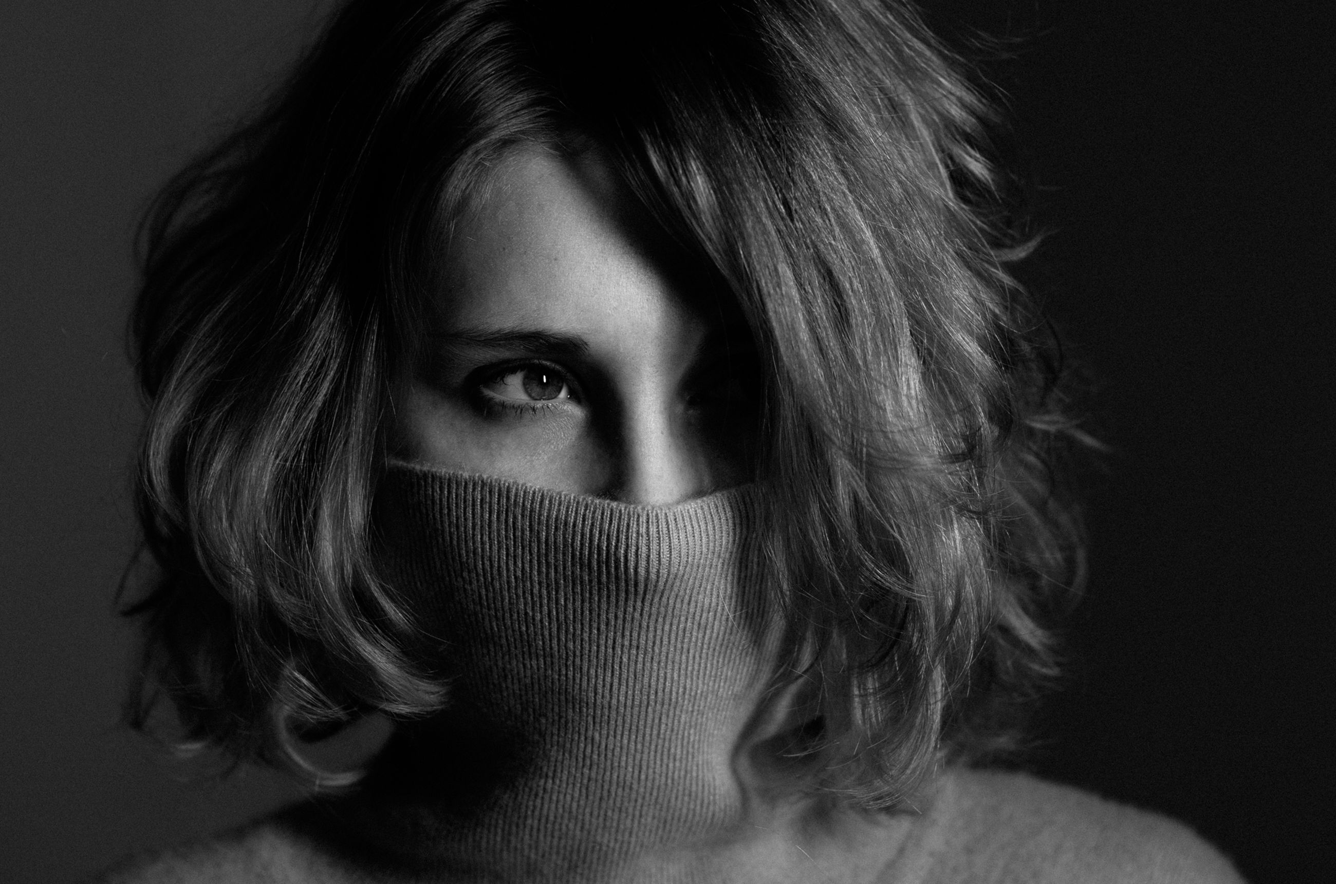 CLOSE-UP OF A YOUNG WOMAN COVERING FACE WITH EYES