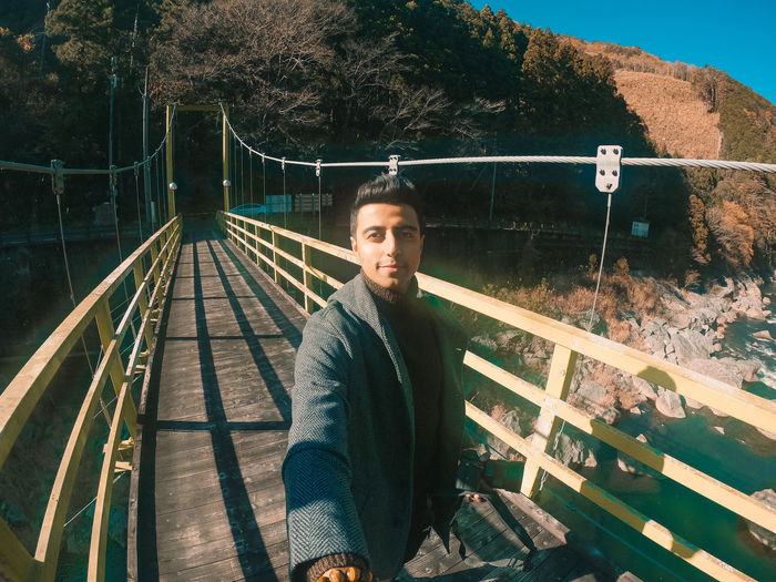 Portrait of young man on footbridge