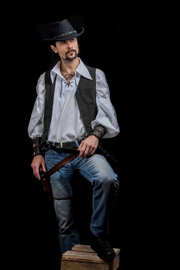 Handsome young man. This is an American cowboy. A vow to a white shirt, brown waistcoat and blue jeans. Black shoes on the feet. Carries a shtyapa, on a belt two pistols. The hair is of medium length; on the face is a beard and mustache. Authentic photo. Culture of America. Cowboy Wild West America American Gun National Authentic Moments Lifestyles Lifestyle One Person Candid Authentic Hat Black Background Clothing Front View Studio Shot Holding Men Three Quarter Length Males  Full Length Standing Mid Adult Men Portrait Mid Adult