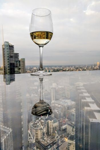 Close-up of wineglass against cityscape