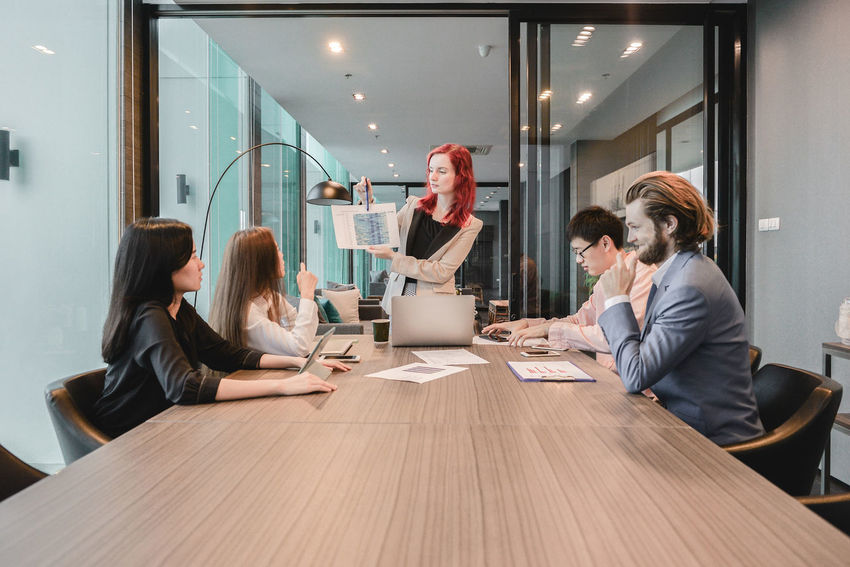 Western business woman boss meeting with her employees in meeting room and sharing ideas, , Multi ethnic Brainstorming Discussing Business Business People Businessman Businesswear Businesswoman Colleague Colleagues Communication Cooperation Coworker Desk Group Indoors  Mature Adult Mature Men Meeting Meeting Room Men Mid Adult Men Multi Ethnic Occupation Office Sitting Table Teamwork Togetherness Well-dressed Western Women Working Young Women