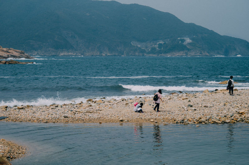 Water Sea Beach Mountain Beauty In Nature Real People Land Men Scenics - Nature Nature Day Lifestyles Group Of People Motion Child People Leisure Activity Wave Childhood Outdoors