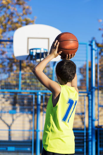 Teenager throwing a basketball into the hoop Adolescence  Arms Raised Ball Basketball - Ball Basketball - Sport Basketball Hoop Basketball Player Blue Boys Child Childhood Day Leisure Activity Lifestyles Males  Men One Person Playing Real People Skill  Sport