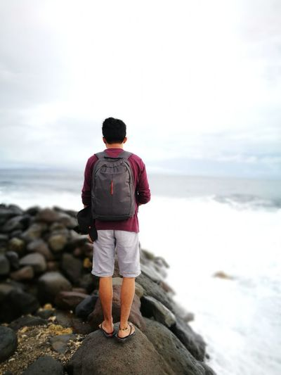 Rear view of man with backpack looking at sea while standing on rock