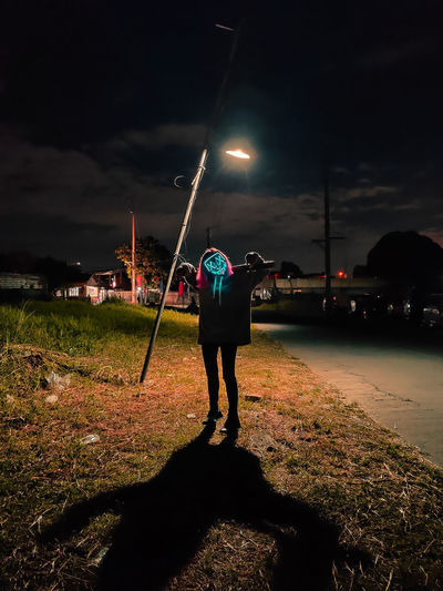 Rear view of man standing on illuminated street light
