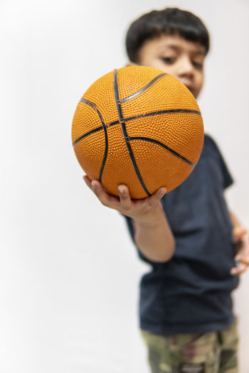Rear view of boy holding ball against white background