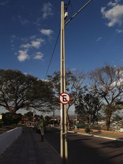 Road sign by trees against sky in city