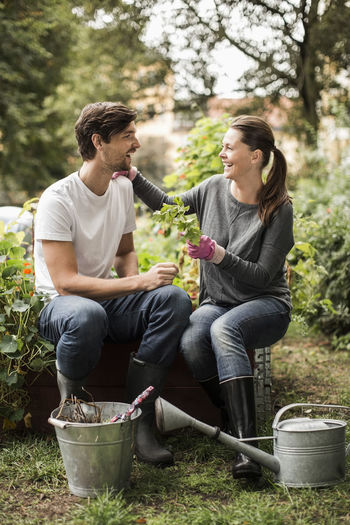 Young couple sitting by plants