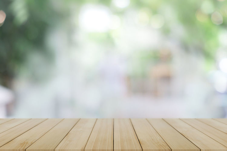 Close-up of wooden bench on footpath