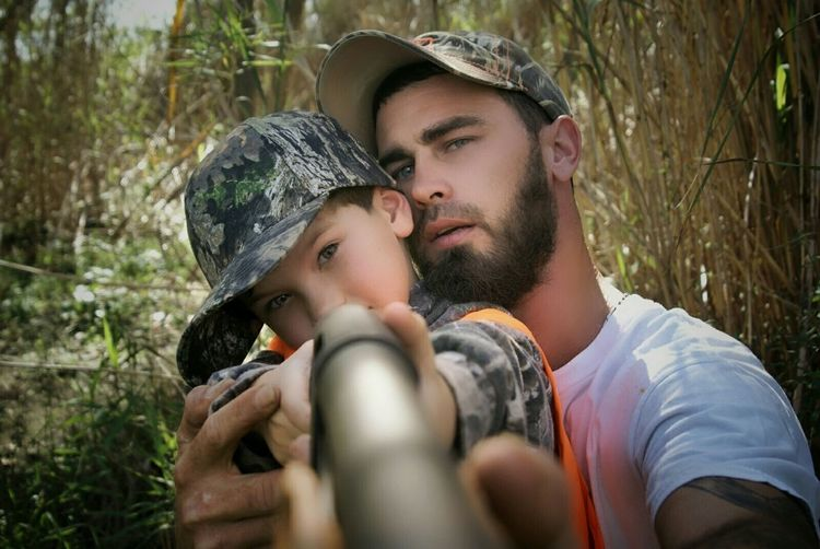 Close-Up Portrait Of Son With Father Holding Gun