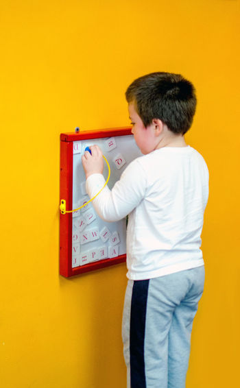this little boy plays with a magnetic pen to drag magnetic letters along a grid and create words and sentences. fun, educational play Fun Learning Boys Casual Clothing Caucasian Child Childhood Colored Background Communication Education Holding Indoors  Innocence Kid Lifestyles Looking Magnetic Board Males  One Person Playing With Words Real People Standing Three Quarter Length Toy Yellow