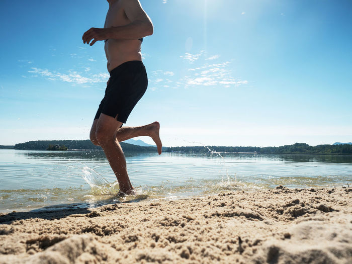 Muscular shirtless man is running in water at the beach.