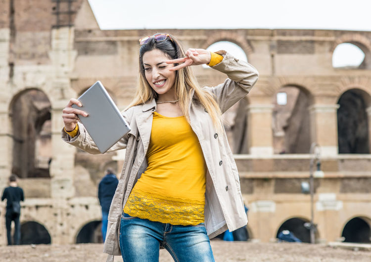 Woman Taking Selfie Against Coliseum