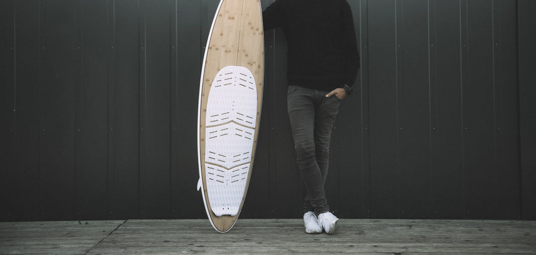 Low section of man with surfboard standing against wall