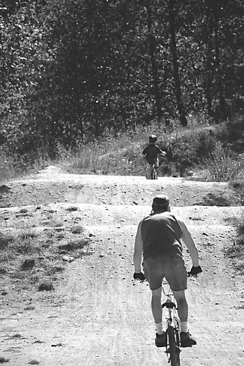 Dad & Son on Bikes This Week On EyeEm. Small Hills...no Bruises Or Scrapes Just Fun. Surrounded By White Ash Trees & Black Berry Bushes. B & W Photography Dad & Son Racing Bikes. Dad Letting Son Win. BMX Track, Fir Tree Landscape, Dusty Trail,