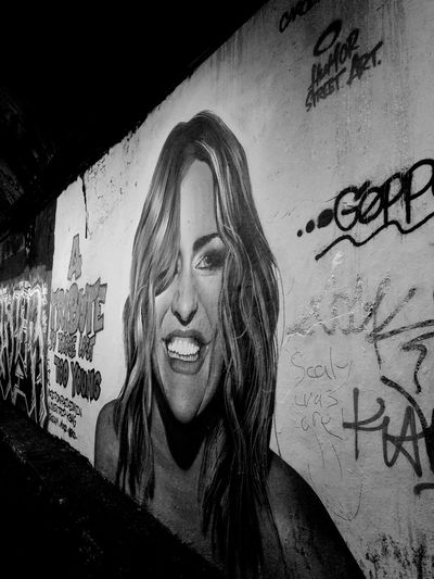 Portrait of smiling young woman against graffiti wall