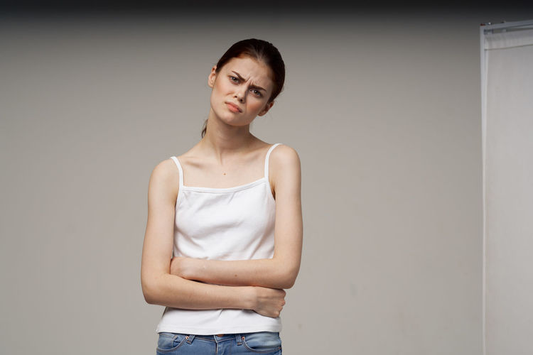 Portrait of a young woman standing against white wall