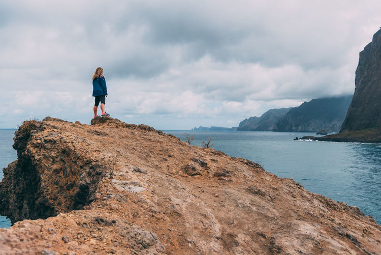 Young woman standing on a rock looking at distant cliffs in a cloudy day. The Crane Viewpoint, Madeira. Lost In The Landscape Beauty In Nature Cloud - Sky Day Full Length Leisure Activity Lifestyles Mountain Nature One Person Outdoors People Real People Rear View Rock - Object Scenics Sea Sky Standing Tranquility Water