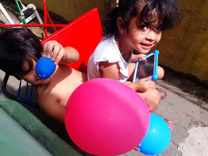 High angle portrait of siblings playing with balloons