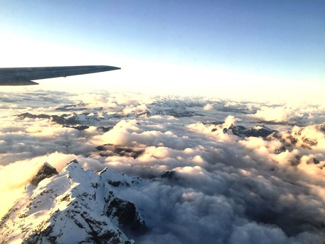 Rocky Mountains peeking through the Clouds From An Airplane Window over Beautiful British Columbia