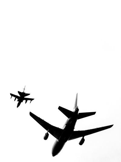 Low angle view of airplanes flying against clear sky