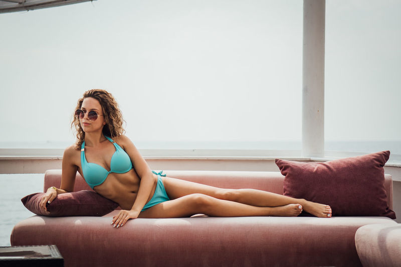 Young Women One Person Lifestyles Young Adult Real People Clothing Full Length Furniture Relaxation Leisure Activity Bikini Sitting Lying Down Women Beautiful Woman Front View Indoors  Swimwear Hairstyle Fashion Hair