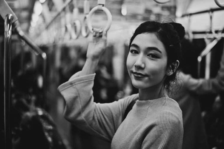 Portrait of beautiful young woman standing in subway train