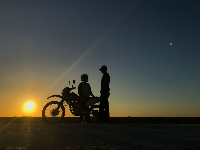 Friends talking while standing by motorcycle on land against sky during sunset