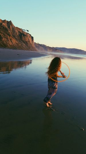 Woman with plastic hoop dancing at beach against sky