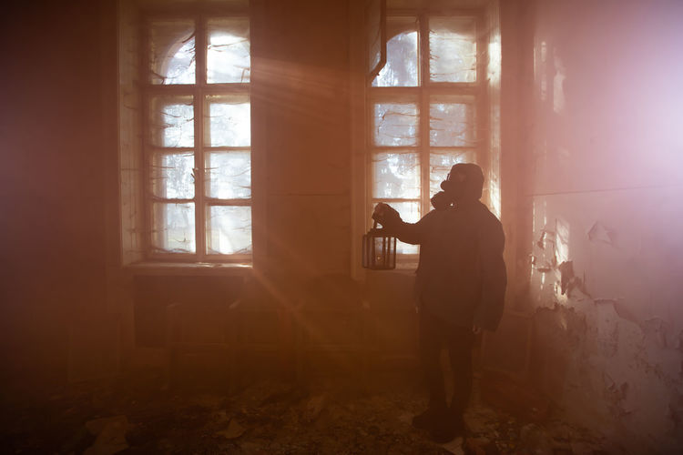 Man photographing through window in abandoned room