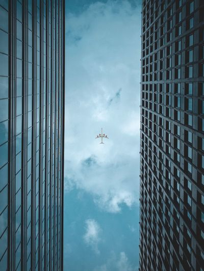 Low angle view of airplane flying over modern building against cloudy sky
