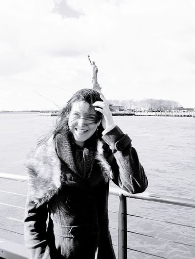 Smiling Woman Standing Against Sea
