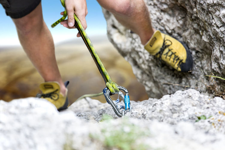 Climber reaches the summit of a mountain. Focus is on the rope and the carabiner Activity Carabiner Climber Climbing Equipment Holding Legs Leisure Activity Mountain Rock Rope, Cord, Cable, Line, Hawser; String; Lasso, Lariat Snap Hook Sport