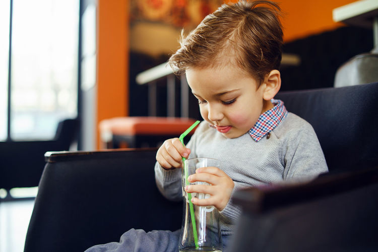 Cute boy holding drinking glass sitting on sofa at home