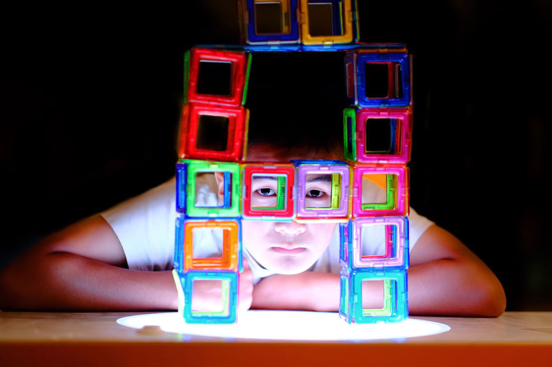 Portrait of boy seen through multi colored toy blocks by table against black background
