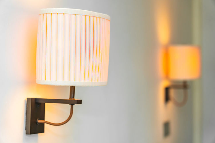 Close-up of electric lamp against wall at home